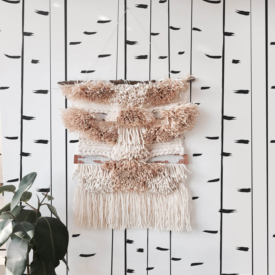 Modern birch tree wallpaper with beautiful blush pink wall hanging in girl's bedroom interior