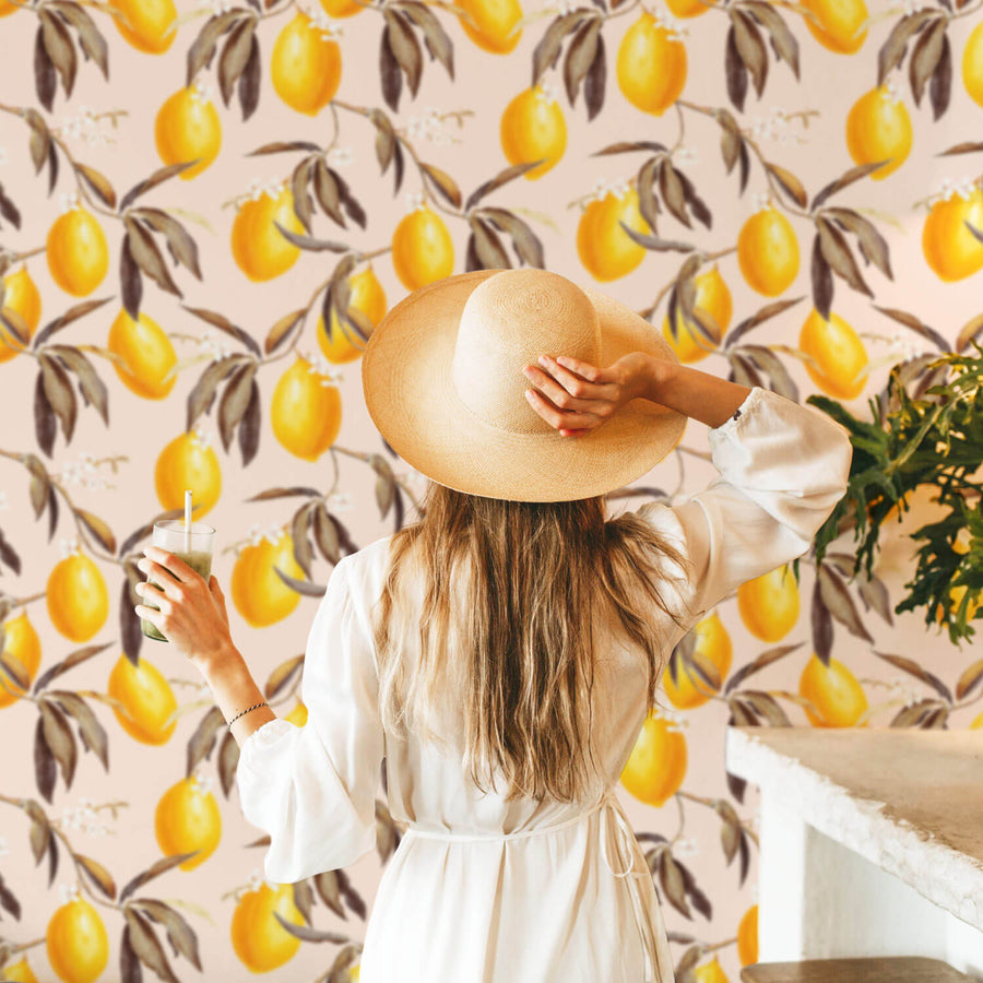 Modern bohemian interior with light pink removable wallpaper with yellow lemons and flowers