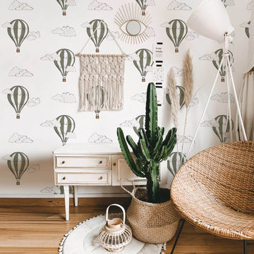 Khaki green watercolor air balloon removable wallpaper in boho interior with cactus and rattan furniture