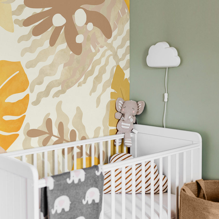 Jungle theme nursery interior with neutral tropical wall mural and safari animals decor and toys