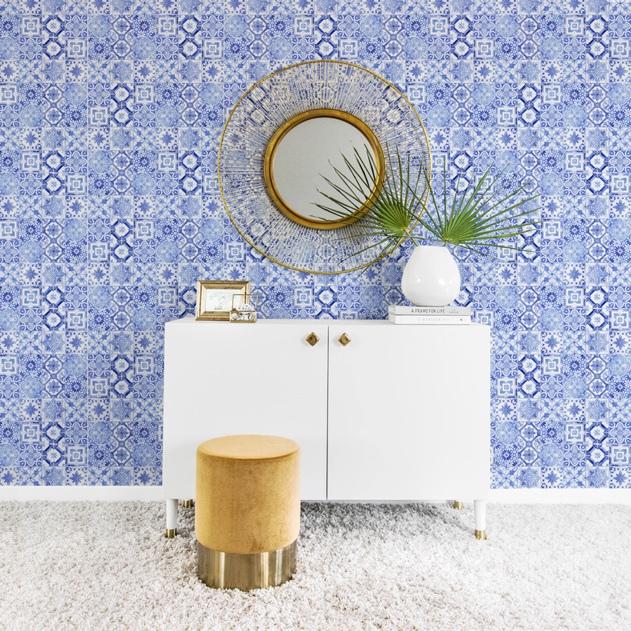 Light blue moroccan tile wallpaper with white dresser and golden stool