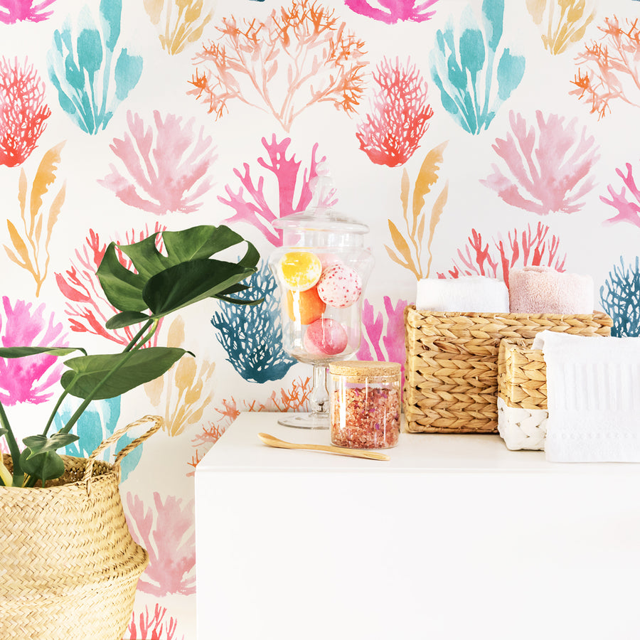 Coral wallpaper in eclectic powder room interior with indoor plants