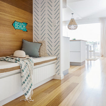 White beach house interior with blue color interior decor elements and light wood accent wall and modern herringbone design removable wallpaper