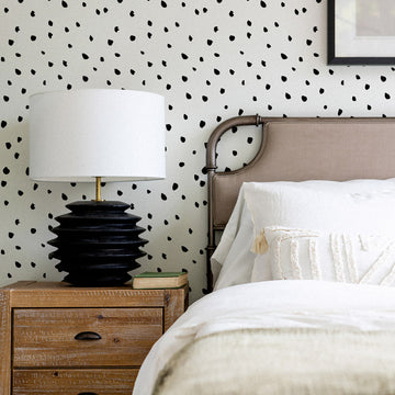 Mid century modern bedroom interior with boho style bedding and speckled removable wallpaper