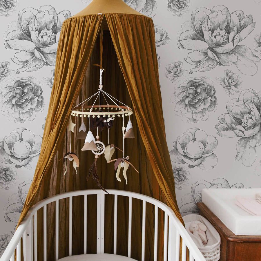 Vintage floral removable wallpaper for bohemian girl's nursery interior with mustard color canopy and baby mobile