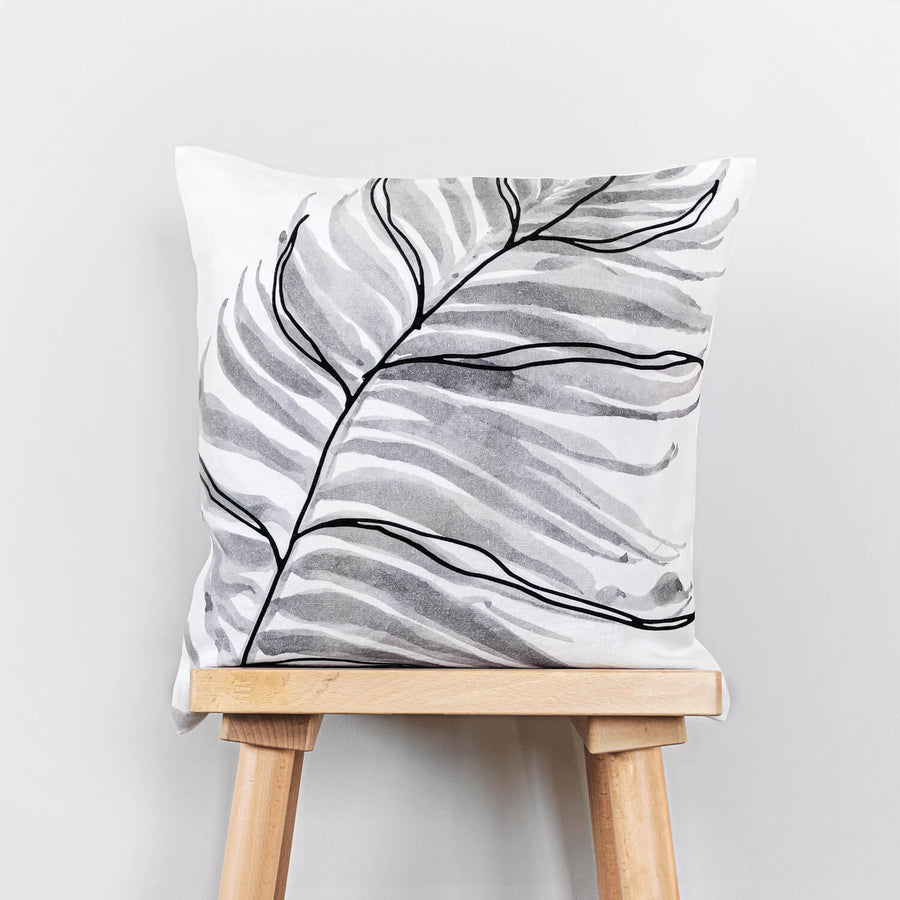 Palm leaf print washed linen cushion cover with black velvet leaf detail