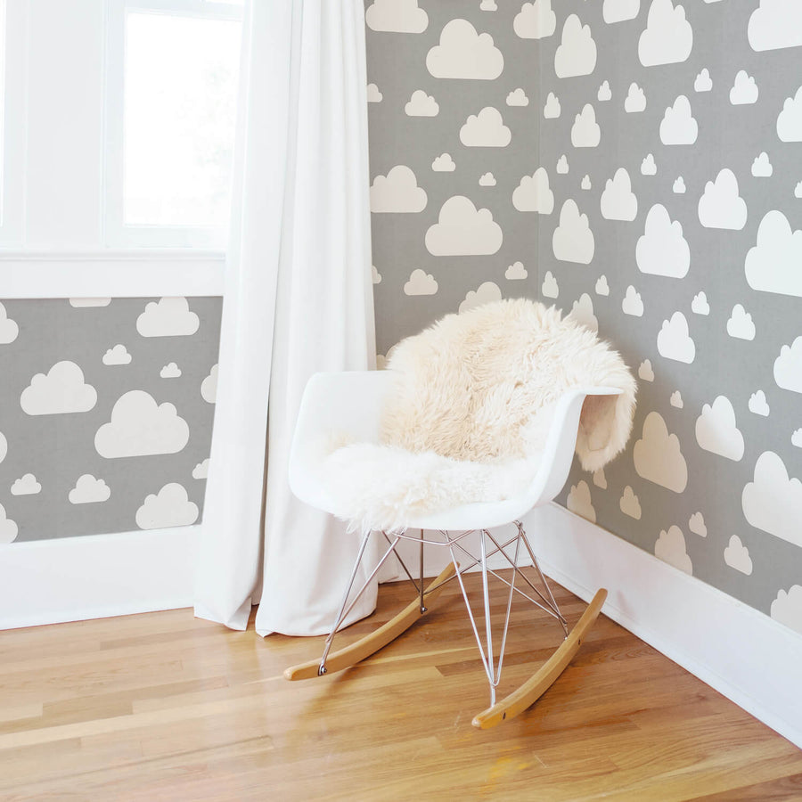 Grey and white cloud pattern wallpaper in soft gender neutral nursery interior with white curtains and wooden flooring