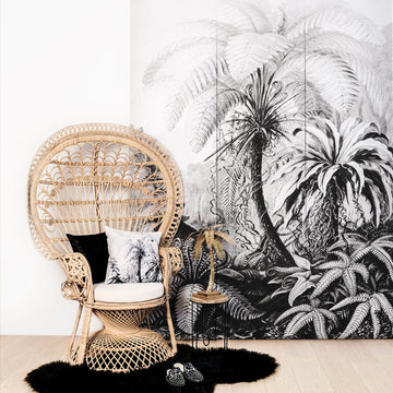 Exotic jungle wall mural in boho living room interior with peacock chair and tropical cushions