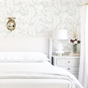 Light green palm leaves removable wallpaper in white bedroom interior