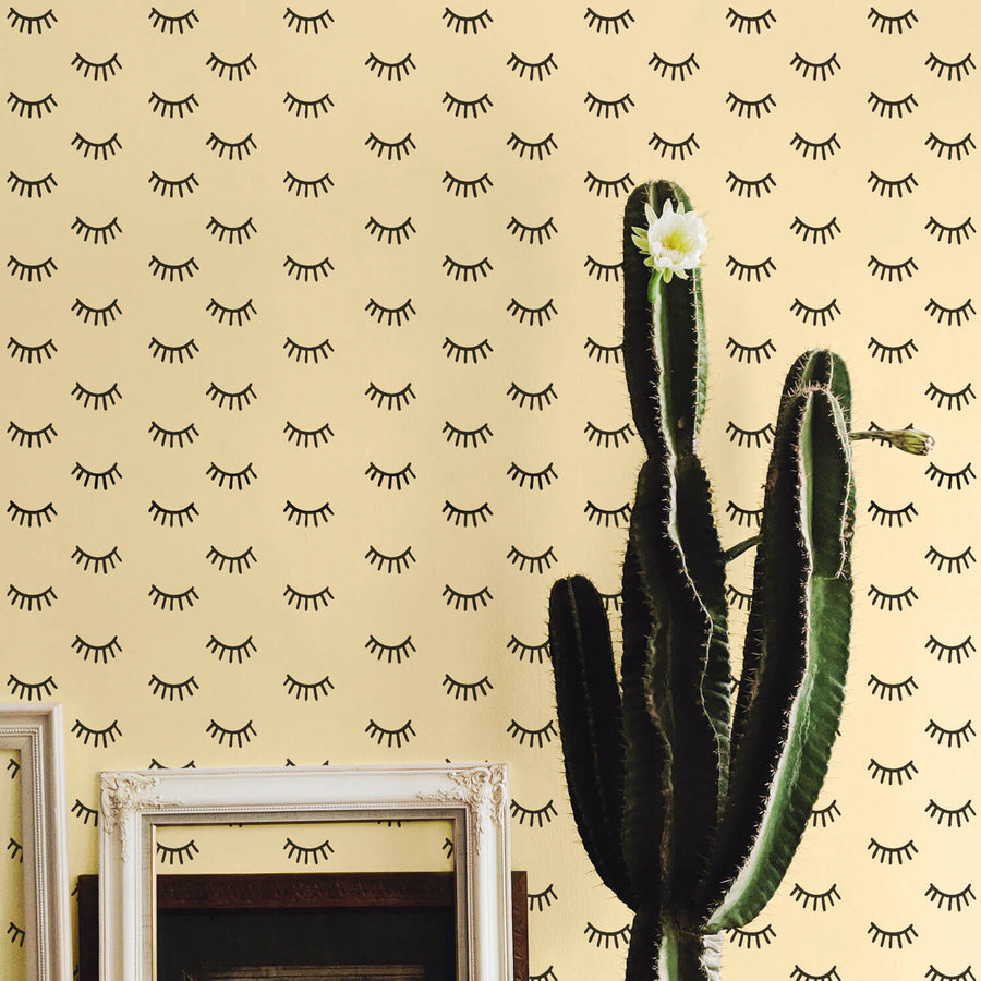 Boho girl's room interior with flowering cactus and sleepy eyes removable wallpaper in yellow and black color