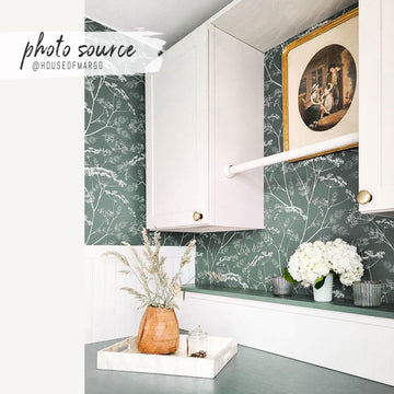 Modern farmhouse laundry room with green botanical removable wallpaper and vintage decor
