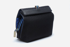 Angled side view of black large deluxe cosmetic clutch displaying secure magnetic closure and elastic pull tab for easy access