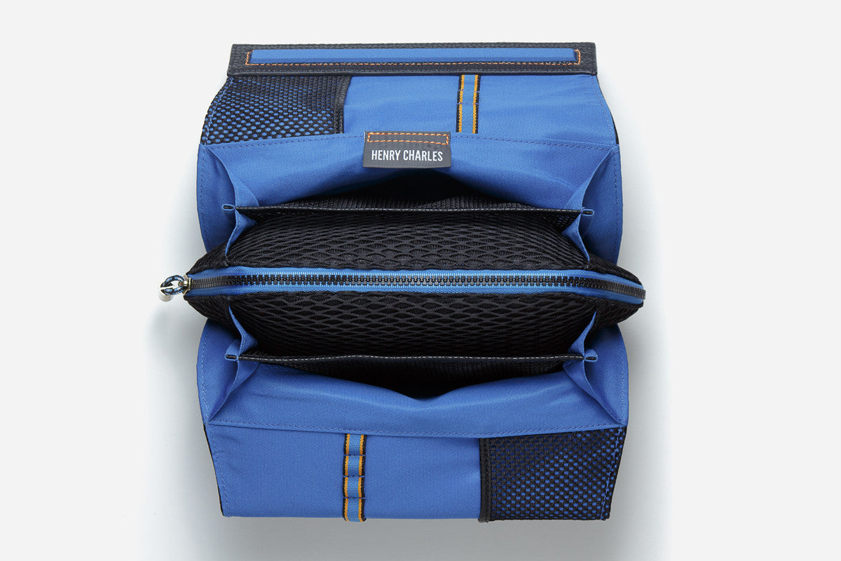 open blue interior view of large deluxe makeup bag displaying zippered pouch in middle and brush holders