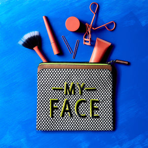 brushes, eye lash curlers, and 3oz skincare spilling outside of Sultry Pop talk back pouch