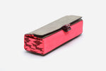 Angled view of pink southwest sunrise brush clutch with easy open elastic pull tabs and metallic top