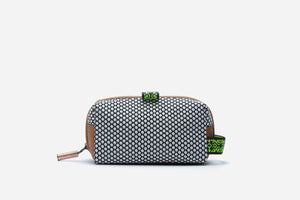 black and white polka dot small cosmetic pouch with brown vegan leather trip, zipper closure, and elastic side handle to attach to luggage or handbag clips