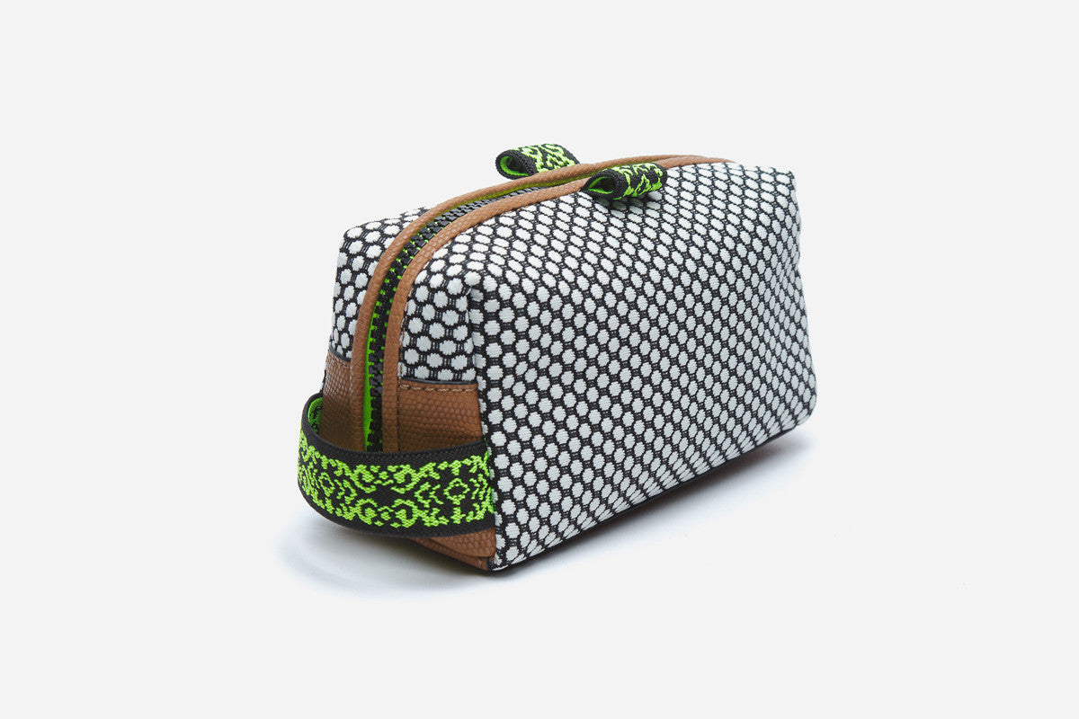 Side angled view of black and white polka dot cosmetic pouchette