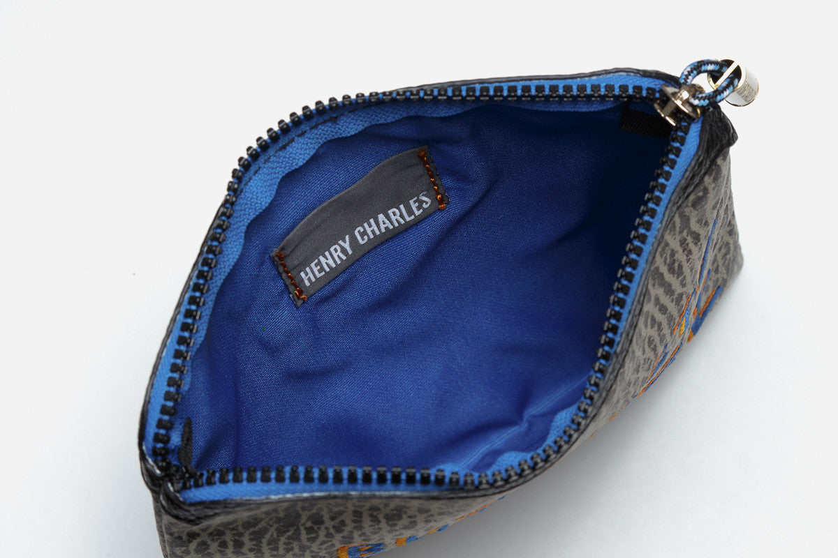 blue interior of black talk back pouchette opened wide to display ample storage