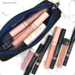 Black zippered case with blue lining holding many lipsticks and lipglosses