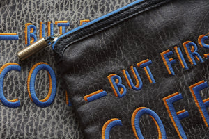 close up of black textured VEGAN LEATHER MATERIAL and blue orange embroidered letters spelling out But First Coffee