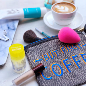 But First Coffee Clutch displayed next to a cup of coffee surrounded by makeup and skincare