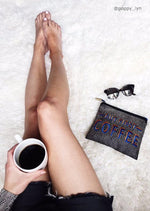 woman's legs on bed with hand holding coffee next to 'BUT FIRST COFFEE' makeup bag