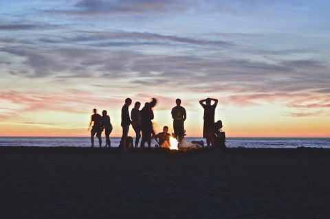 People camping on a beach with a bonfire