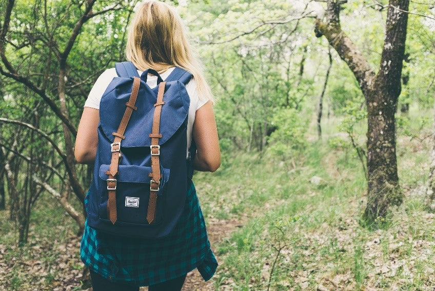 A person hiking through a forested area with a backpack