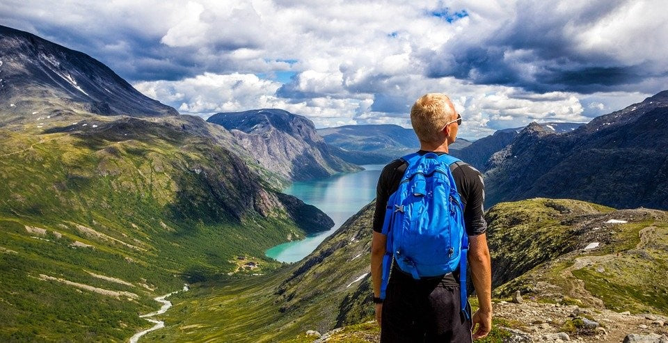 A hiker looking over a mountain valley with a blue backpack