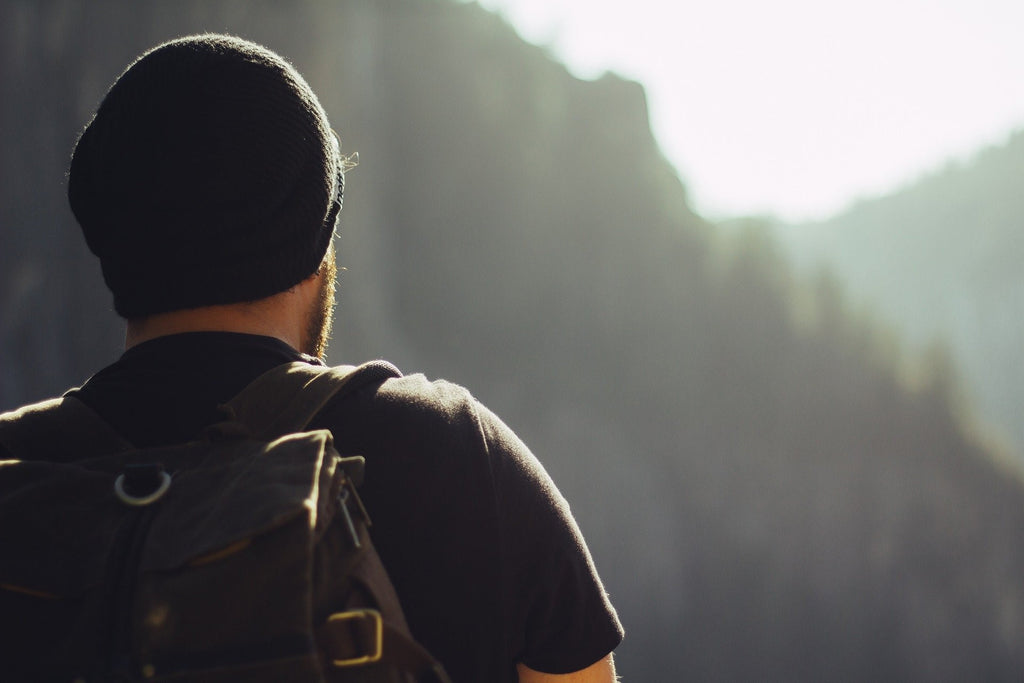 A person hiking with a beanie and backpack on