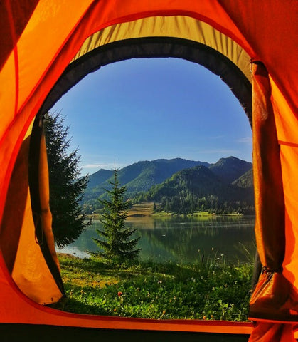 An orange tent with a view of a lake and hills