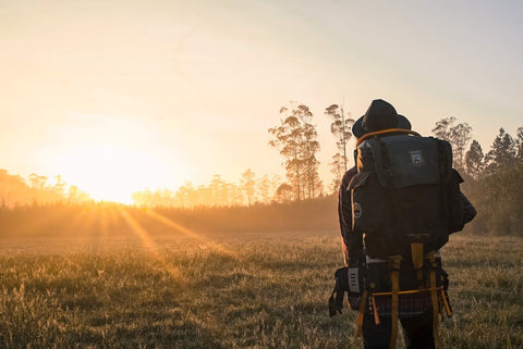 A man with a backpack during sunset