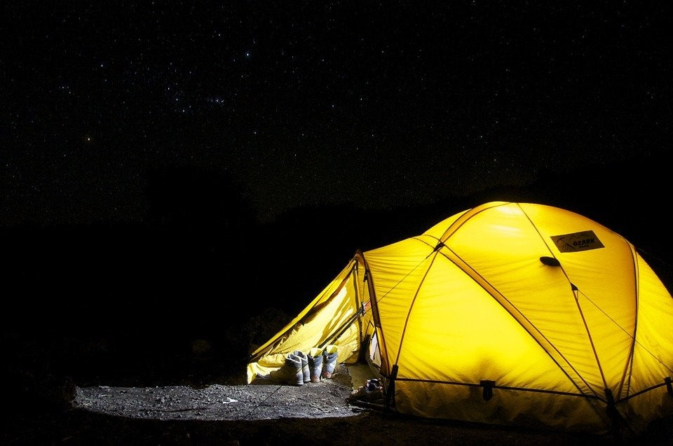 A yellow tent tied to the ground