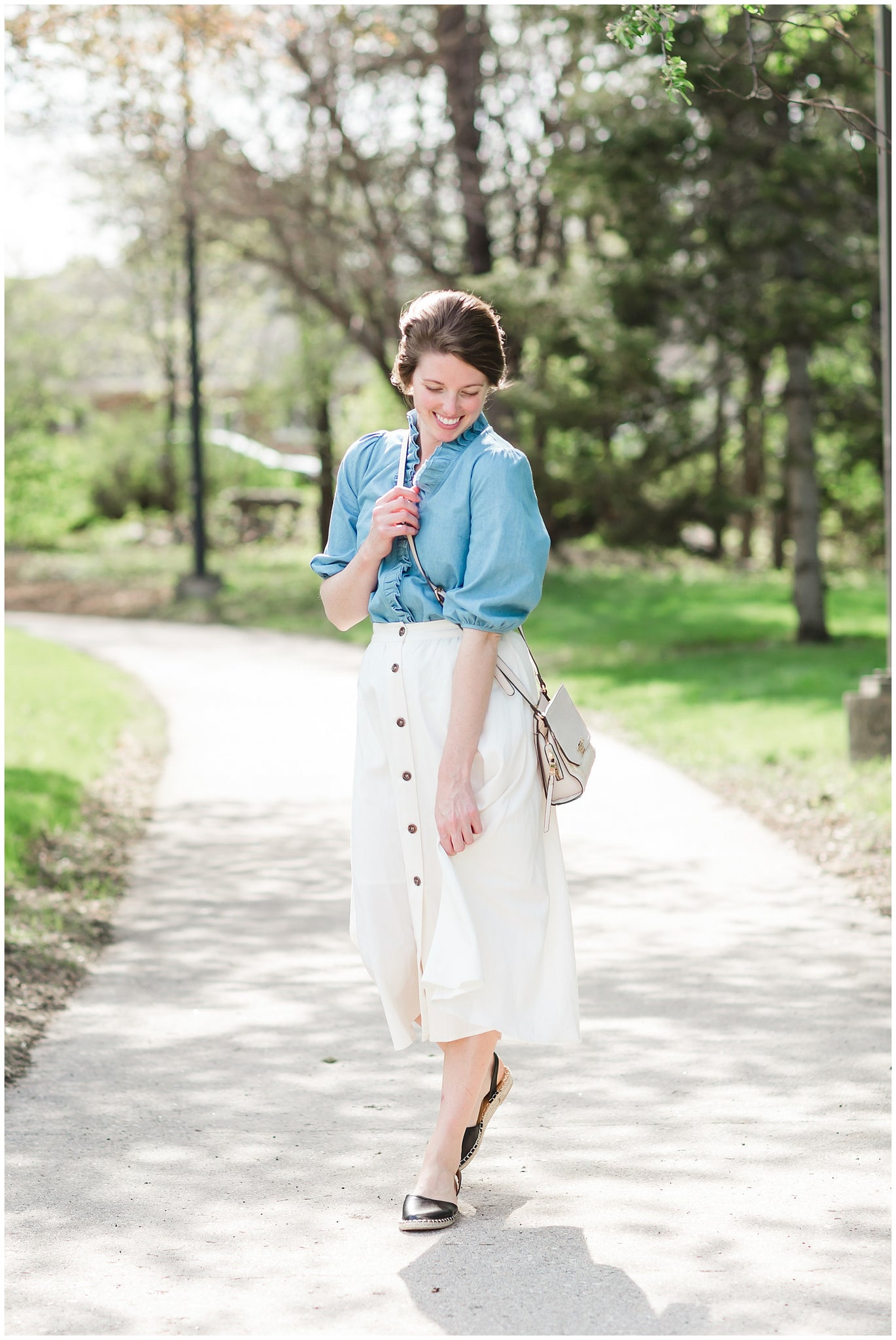 Female in midi length white a-line skirt with denim blouse, crossbody handbag and black sandals