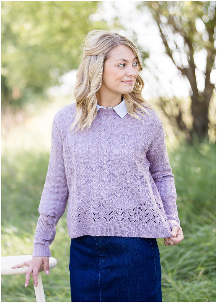 lavender crochet sweater layered over a button up blouse paired with a denim skirt