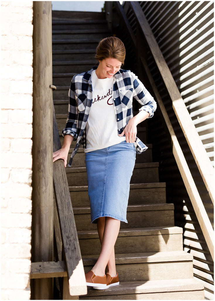 woman wearing a weekending graphic tee paired with a navy flannel shirt and a denim jean skirt