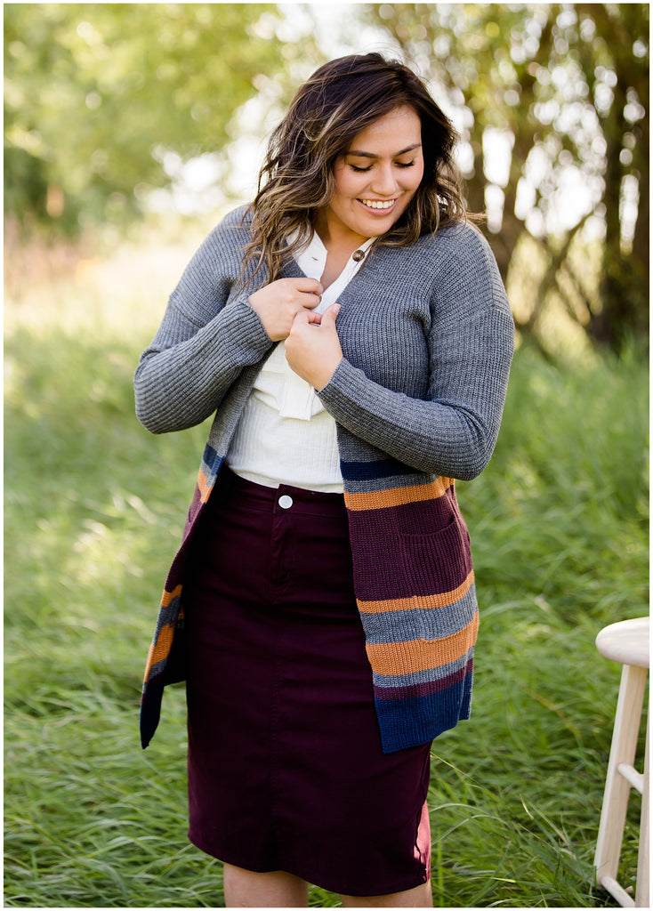 woman wearing a colored denim skirt with a burgundy, gold and gray long duster cardigan