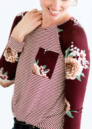 Woman wearing a modest burgandy floral and stripe long sleeve top with a twist front hem.