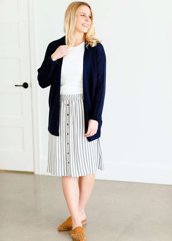 Woman wearing a gray striped skirt with camel colored faux buttons on the front that also has an elastic waistband