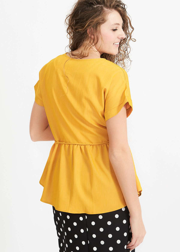 Woman wearing a mustard peplum style blouse with a self tie fabric belt
