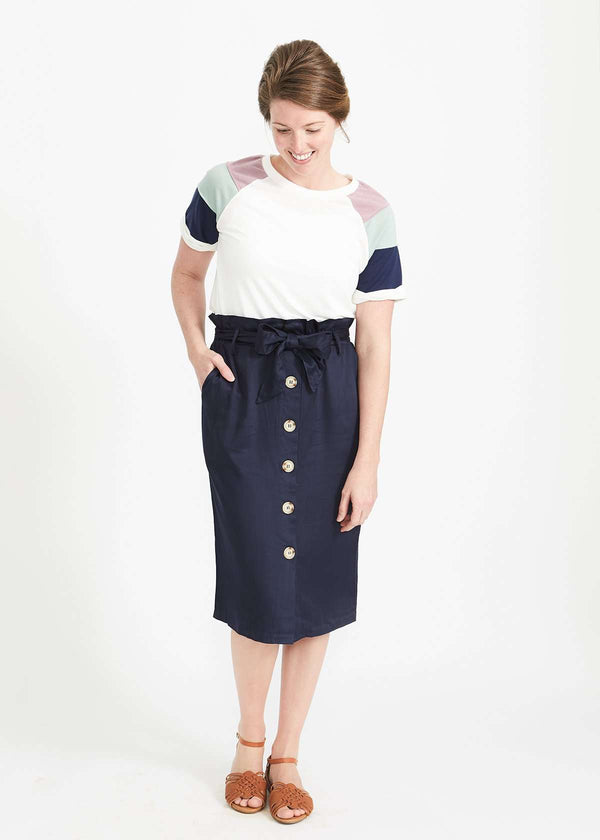 6655e9b43709 Woman wearing a navy button front paper bag style midi skirt.