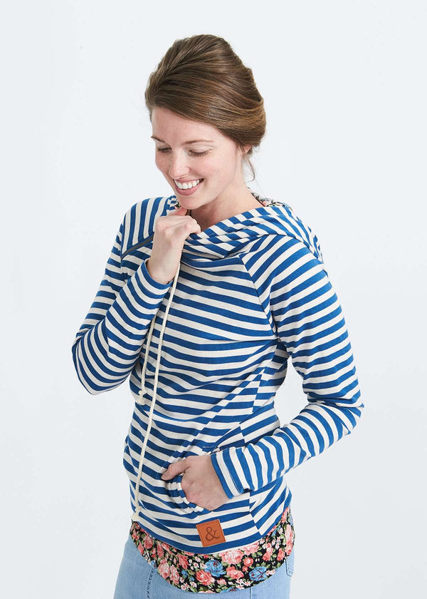 Woman wearing a blue and white striped double hood sweatshirt with floral accent