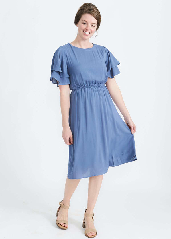 25951aa750be woman wearing a dusty blue empire waist dress with double ruffle sleeves  that is lined and