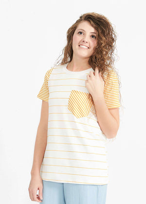 Woman wearing a striped tee with mustard sleeve and pocket accents