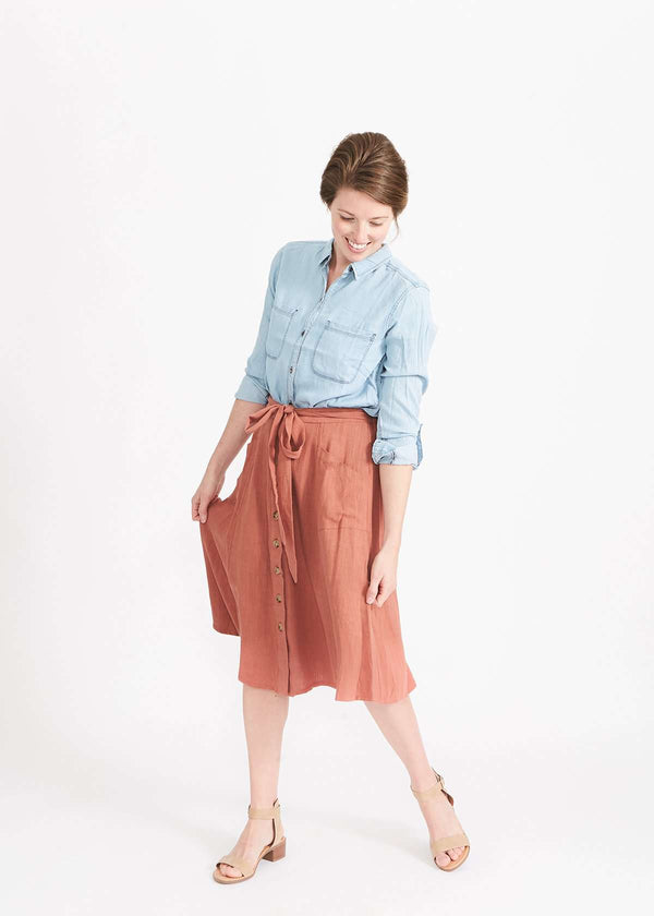 Woman wearing a button front self tie pink midi skirt with big pockets and paired with dress heels and chambray top