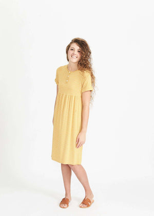 Woman wearing a below the knee mustard and stripe midi dress with buttons on the bodice and hidden pockets