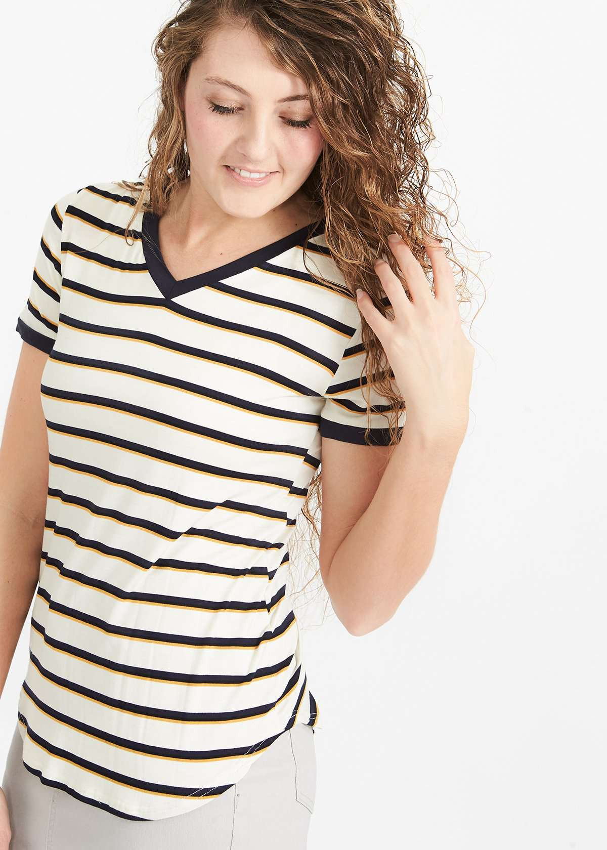 Woman wearing a navy and mustard striped modest v-neck tee