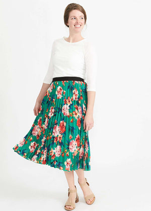Woman wearing an emerald green floral stretchy pleated swing skirt with dress shoes and a white lace top