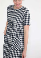woman wearing a navy and white gingham print midi dress