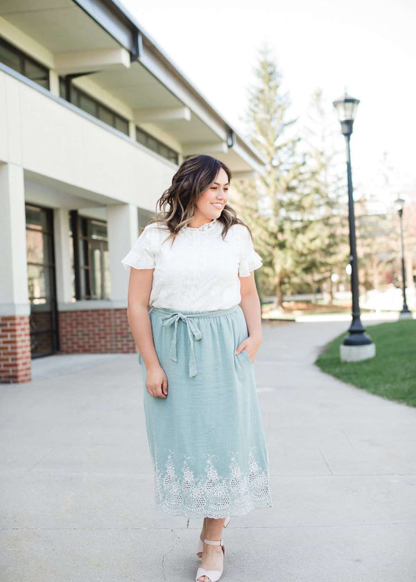 005e93f6b9 Woman wearing a mint green cotton midi skirt with a self tie and feminine  crochet lace